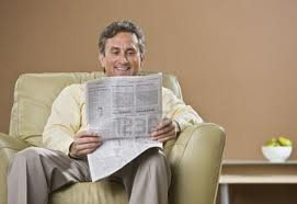 He is sitting down reading a newspaper
